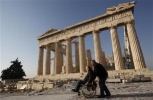 A man pushes a disabled man on a wheelchair in front of the Parthenon temple during a protest atop the Acropolis hill in Athens