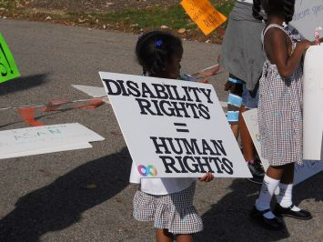 "Bimba con cartello in mano ove è scritto: ""Disability Rights = Human Rights"""