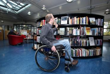 Persona in carrozzina in una biblioteca accessibile