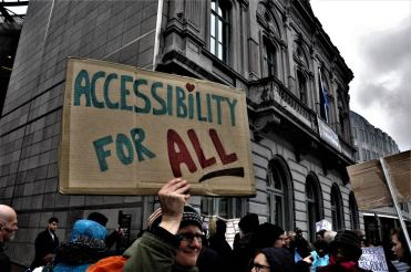 "Persona con cartello recante la scritta ""Accessibility for All"""
