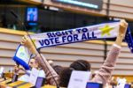 "Una persona con disabilità solleva una sciarpa, all'interno del Parlamento Europeo, con la scritta ""Right to Vote for All"" (""Diritto di voto per tutti"")"