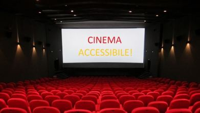 "Sala cinematografica. Sullo schermo la scritta ""Cinema accessibile!"""