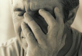 Viso di uomo con mano sul volto ed espressione di sconforto