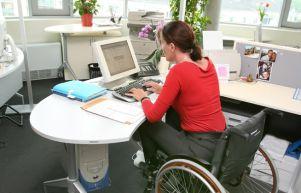 Donna in carrozzina al lavoro al computer