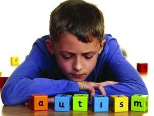 """Ragazzo con dei cubi colorati davanti, che compongono la parola """"Autism"""""""