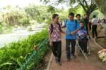 Un giovane non vedente e un giovane con disabilità motoria in carrozzina percorrono un sentiero turistico insieme ad altre persone