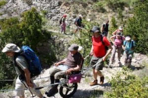 Una persona con disabilità in montagna, sulla speciale carrozzina joelette