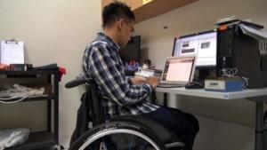 Giovane in carrozzina lavora al computer