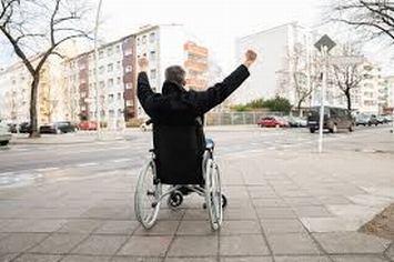 Uomo con disabilità in carrozzina fotografato di spalle con le braccia levate