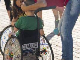 Un bimbo con atrofia muscolare spinale insieme a una componente dell'Associazione Famiglie SMA