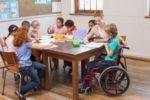 Un'assistente all'autonomia e alla comunicazione insieme a un bimbo con disabilità