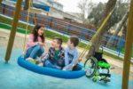 Bambini con e senza disabilità in un parco giochi accessibile