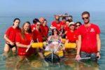 Sandra Pratali mentre fa il bagno in mare a Tirrenia (Pisa), con il supporto delle persone dell'Associazione Team Deri SLA
