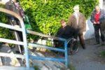 Una persona con disabilità motoria bloccata dalle barriere davanti al ponte pedonale che collega la Stazione di Ostia Antica al Parco Archeologico