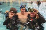 Una persona con disabilità insieme a due istruttori dell'Associazione ATIS Diving Club